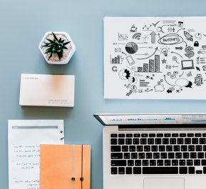 Kuvassa vaaleansinisellä taustalla siisti työpöytä, jossa kannettava tietokone, muistivihko, pieni viherkasvi sekä mindmap-tyylinen piirrustus.
